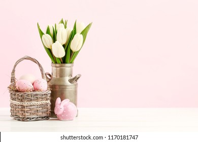 Pink Easter decorations: tulip flowers, basket with painted eggs and dotted rabbit figure on white wooden table.