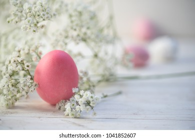 pink easter egg and gypsophila (baby breath flower) on white painted rustic wood with copy space, selected focus, narrow depth of field
