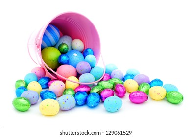 Pink Easter pail spilling colorful chocolate eggs and candy