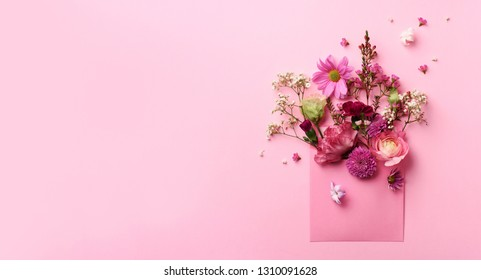 Pink envelope with spring flowers. Floral composition, creative layout. Flat lay, top view. Spring, summer or garden concept. Present for Woman day.