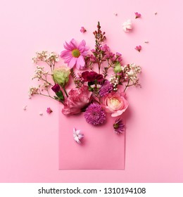 Pink envelope with spring flowers. Floral composition, creative layout. Flat lay, top view. Spring, summer or garden concept. Present for Woman day. Square crop.
