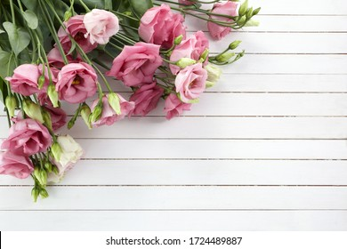 Pink eustoma flowers on wooden background in vintage style. Romantic wedding background. Top view.