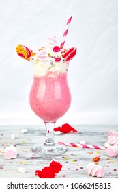 Pink Extreme milkshake with berry, rasberry, strawberry, candy marshmallow, lollipops on white background. Crazy freakshake. Copy space. Food trend. Overshake