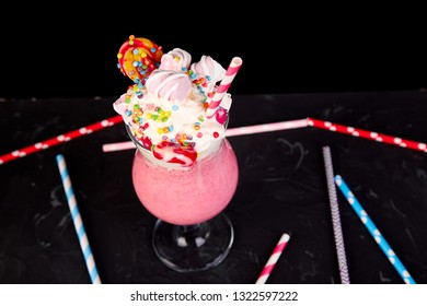 Pink Extreme milkshake with berry, rasberry, strawberry, candy marshmallow, lollipops on black background.. Crazy freakshake. Copy space. Food trend Overshake