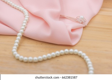 Pink fabric and pearl necklace on wooden table with copy space.