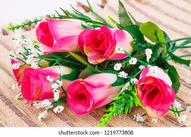 Pink fabric roses on beige bamboo background.
