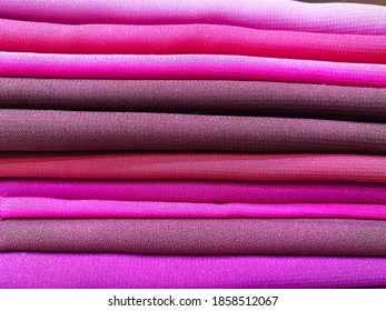 Pink fabrics folded on top of each other.