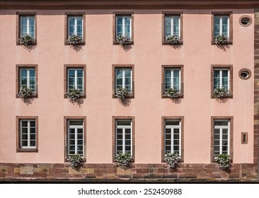 """Pink facade of a building with windows and flowers in pots in the historic district """"Petite France"""" in Strasbourg, Alsace, France"""
