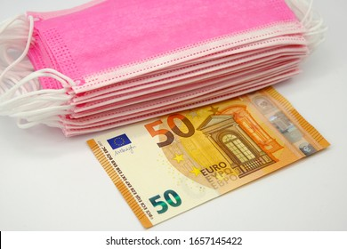 Pink face masks for virus protection and 50 euro banknote. Concept for high price of surgical masks during the epidemic in Europe.