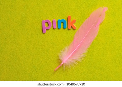 A pink feather with the word pink on a yellow background