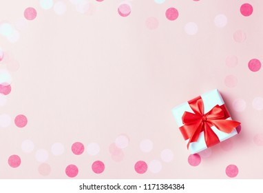 Pink festive holiday background with goft box and pink confetti. Copyspace for your text.