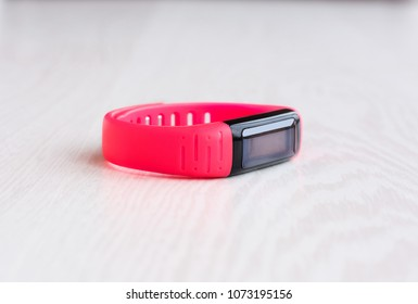 Pink fitness bracelet with place for text on a white wooden background