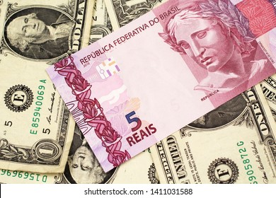 A pink five reais bank note from Brazil close up in macro with a background of United States one dollar bills