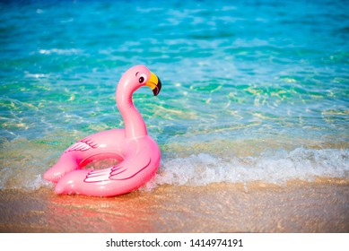 Pink flamigo ring tube in sea water. Kids water safty accessoires.