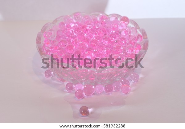 Pink flavored balls in a small glass container