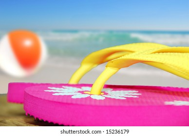 Pink flip flop sandals on dock next to beachball and ocean