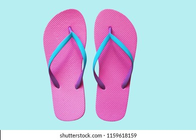 Pink flip flops isolated on blue background. Top view