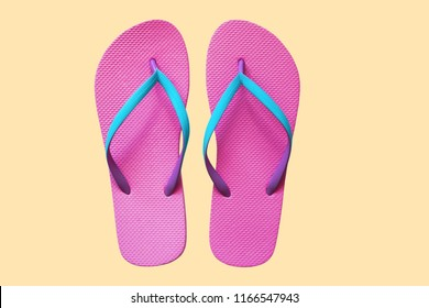 Pink flip flops isolated on yellow background. Top view