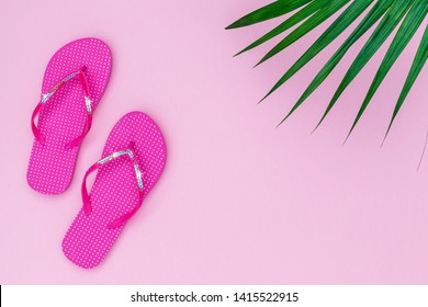 Pink flip flops shoes with sequins on pink background, top view, with copy space. Toe sandals in polka dot, flat lay, text place. Summer background with flipflop shoes and palm leaves.