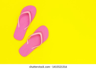 Pink flip-flops shoes on yellow background, top view, copy space. Toe sandals, flat lay, text place. Summer background with flipflop shoes.