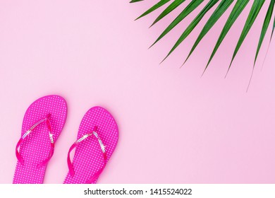 Pink flipflops shoes with sequins on pink background, top view, with copy space. Toe sandals in polka dot, flat lay, text place. Summer background with flip flop shoes and palm leaves.