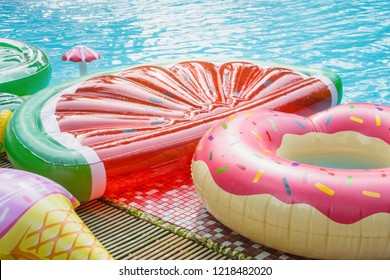 Pink floating donut, water melon beside swimming pool. summer and vacation concept.