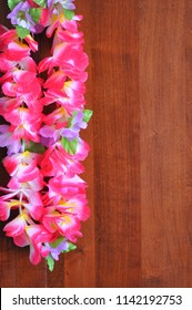 Pink floral Hawaiian lei isolated on wooden background