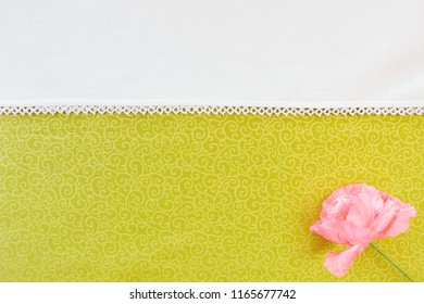 Pink flower on textile background shot from above with white space and copy space.