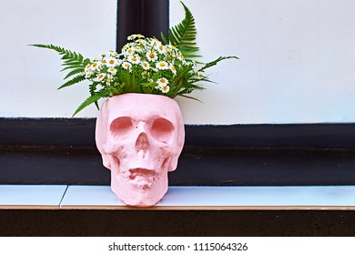Pink flower pot in the form of a skull on a outdoor shelf at a street cafe