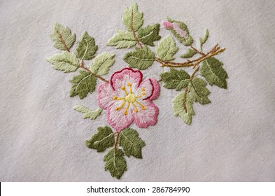 Pink flower embroidered satin stitch on rough  cotton cloth