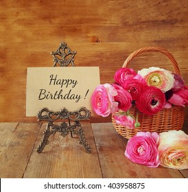 pink flowers in the basket next to card with phrase: happy birthday, on wooden table.