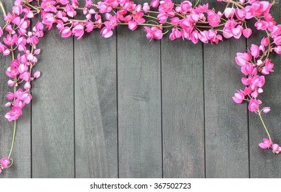 Pink flowers (Confederate vine or Coral vine) and wood