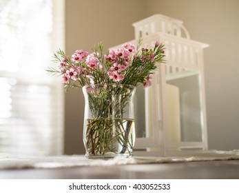 Pink flowers in glass vase with off-focus candle lamp in the back