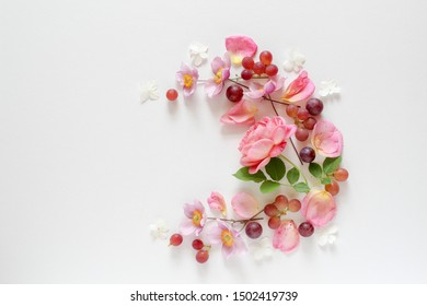 Pink flowers and grapes arranged in a wreath on a bright background with a copy space