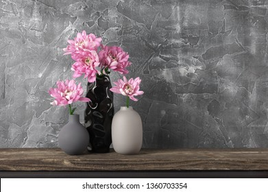 Pink flowers in neutral colored vases on distressed wooden shelf against rough plaster grey wall. Home decor.