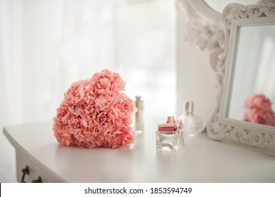 Pink flowers on the dressing table in the white bedroom. Flowers and perfumes in a bright interior. White boudoir table close up and copy space.