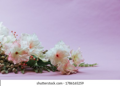 Pink flowers on a violet mauve background, perfect for greeting cards with empty space