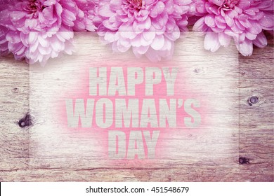 pink flowers on wooden with word Happy Woman's Day