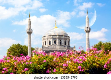 Pink flowers with Pertevniyal Valide Sultan Mosque, an Ottoman imperial mosque in Istanbul, Turkey. Summer sunny day with blue cloudy sky and crescent moon. Islam, moslem and Ramadan concept.