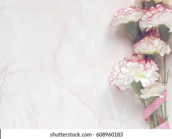 Pink flowers with pink ribbon on light marble background. Flat lay. Top view
