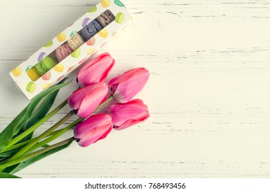 Pink flowers Tulips and gift box with macaroons on white rustic wooden table with place for text. Present on Mothers day, Valentines Day or Womens day. Gritings woman concept. Top view. Copy space.