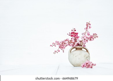 Pink flowers in vintage vase on a stylish white background. Beautiful fantasy romantic minimalist still life. Space for text