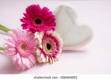 pink flowers and a white painted wooden heart on a pastel colored background, love symbol for valentines or mothers day, copy space, selected soft focus
