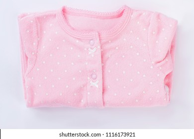 Pink folded baby pajamas isolated on white. Neatly folded neborn baby girl clothes decorated with dots.