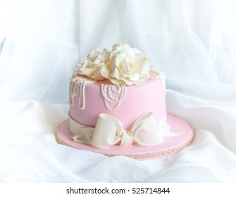 Pink fondant cake with roses, pearls and bow