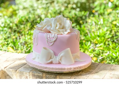 Pink fondant cake with white roses and pearls