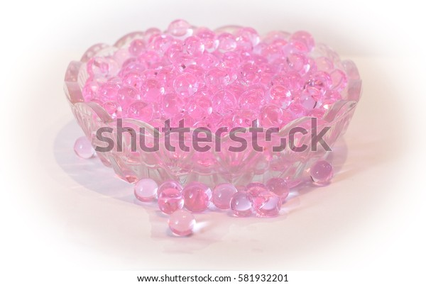 Pink fragrant droplets in a small glass bowl