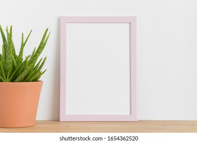 Pink frame mockup with a aloe vera in a ceramic pot on a wooden table. Portrait orientation.