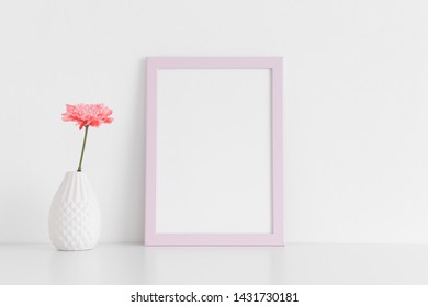 Pink frame mockup with a chrysanthemum in a vase on a white table. Portrait orientation.