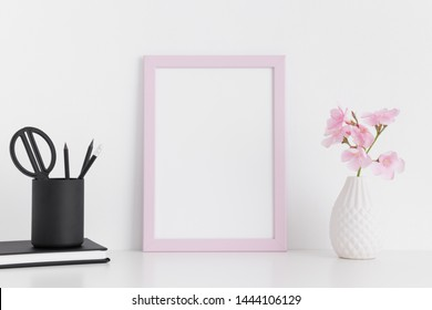 Pink frame mockup with pink oleander in a glass vase and workspace accessories on a white table.Portrait orientation.